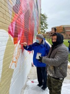 Professor emeritus David Schultenover, S.J., (left) and mural artist Mauricio Ramirez (right) take part in the Haggerty Museum Community Paint Day as work progresses on the mural at Marquette University